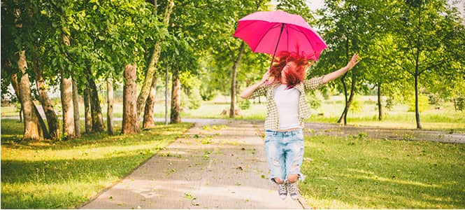 woman jumping with a pink umbrella